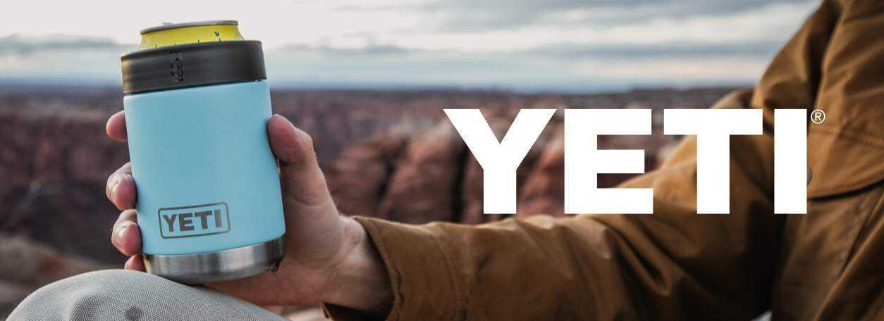 YETI logo with person holding YETI product near canyon